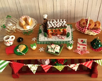 Miniature Christmas Table With A Gingerbread House, A Cake On Hand Painted Glass Cake Stand, A Snowman Mug With Cocoa, And More