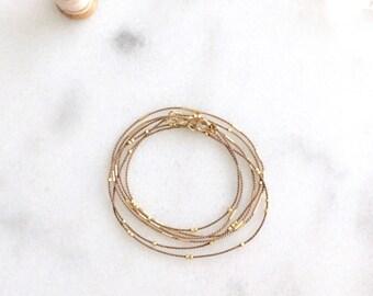 tiny gold beaded triple wrap silk cord layering bracelet.