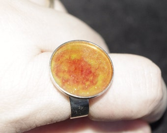 This ring is adjustable and pigmented in shades of orange and Red resin