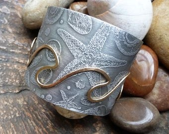 Undertow Cuff is an etched pewter sealife cuff embellished by my shaped and hammered golden waves all around.