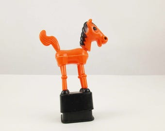 An Orange Floppy Spring Horse - Child's Toy - Plastic Spring Toy - Orange With Black - Push Down and Collapse - Hong Kong