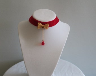 Red velvet choker necklace with gold bow and crystal pendant
