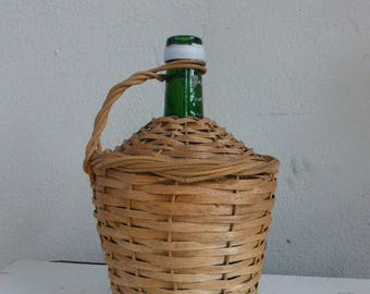 Thick green glass bottle, dressed in vintage wicker.