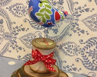 Fabric bird on vintage cotton reel