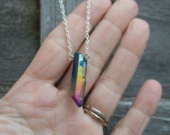 """Bright and vibrant rainbow-hued aura Quartz crystal point, its drilled and made into a lovely hanging necklace. Silver plated 18"""" chain."""