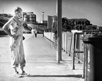 Tourist photo, Black White print, woman tattooed arm, hands on hips, dungarees overalls, summer promenade, Norfolk UK, candid photography,