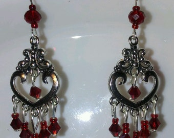 Silver tone chandelier earrings with red crystals.