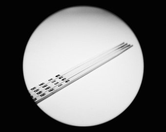 Photography black and white cuicine utensils: chopsticks, Chinese calligraphy.