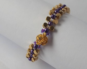 A dark purple and gold cubed beaded bracelet with clear crystals on a gold plated magnetic clasp with a safety chain