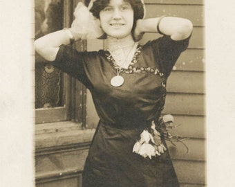 vintage photo 1913 Pretty woman Tulip flowers hang From Dress Arms Up Hair Bow RPPC