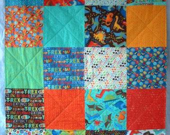 "Dinosaurs cot quilt, ready to ship. Moda 'Jurassic Jamboree' red, blue, aqua, green, orange, patchwork. Modern design. 36"" x 45"". Lap quilt."