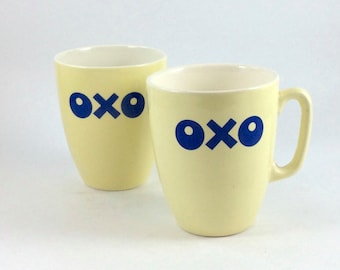 OXO coffee mugs or tea mugs. Vintage pastel yellow ceramic with dark blue logo. For home use, coffee house, café, restaurant.