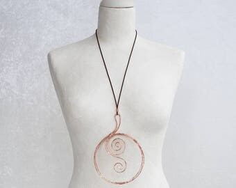 A necklace made of copper wire with a large, round pendant totally handmade. A very special jewel.