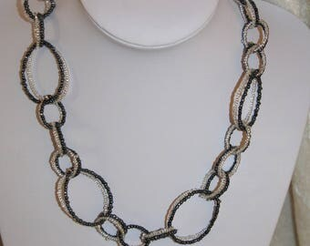 Necklace with black-grey and white shiny rings
