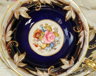 Aynsley, England: Pedestal blue cobalt tea cup & saucer with hand painted flowers by Bailey