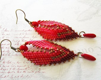"""Woven earrings shaped """"leaves"""", and red tones."""
