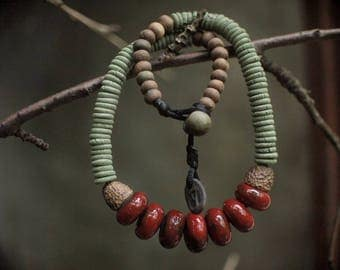 Necklace with glazed red and unglazed green flat beads.