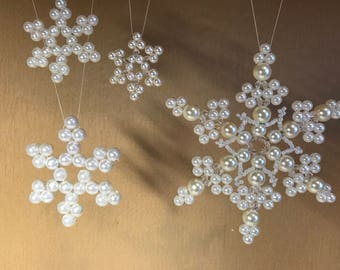 Set of hand-made snowflakes for a Christmas tree. Ornament of white pearls. Winter festive decor. A gift for loved ones.