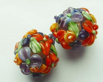 glass lampwork bead set in purple with raised flower decoration