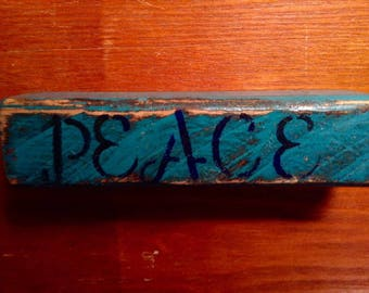 "Wooden decoration,  plaque, sign,  with the word ""Peace"" painted on it."
