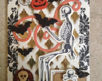 Halloween Card (Ghastly Greetings)/Handmade Card/3D/Front features a Skeleton Holding a Large Bat & Surrounded by smaller Bats