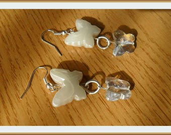Plastic butterfly earrings and white and transparent glass.