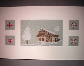 Painting of a snowy cottage and snowflakes