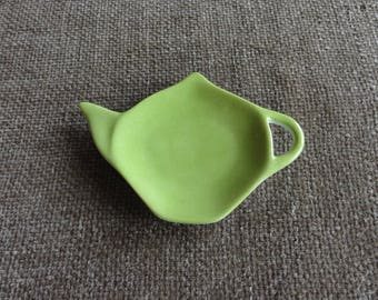 Is white porcelain Teacup handpainted lime green.
