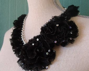 Silver chain adorned with glittery flowers and ruffles.