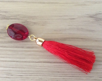 Red tassel and faceted flat oval bead pendant