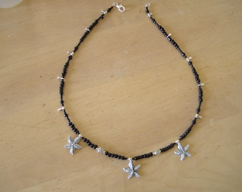 Black glass beads and (tears) beads and silver plated stars.