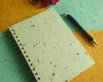 Ecological ringed notebook with incrustations of dry leaves of oregano