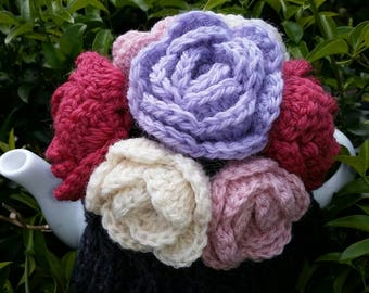 Dark gray hand knitted tea cosy with dusty pink,purple, white,  red hand crocheted flowers, tea pot is not included.