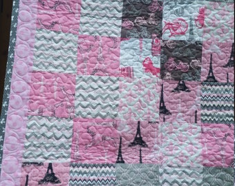 Beautiful baby quilt pieced with fabric with Paris bicycle polka dots in greys and pink