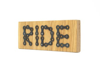 Wooden sign with RIDE in bicycle chain