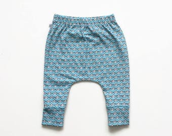 Slim fit harem pants with small boats. Baby or infant pants. Light blue jersey knit fabric. Kids leggings with cuffs. Boy or girl