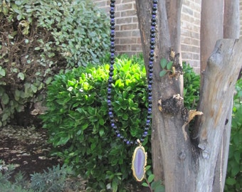 Long 21'' purple and black beaded necklace with a purple rock
