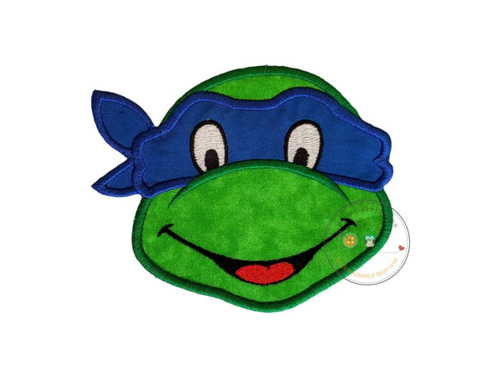 Blue-masked turtle head iron on patch in bright green fabric trimmed in green with blue fabric for the mask trimmed in blue detailed eyes