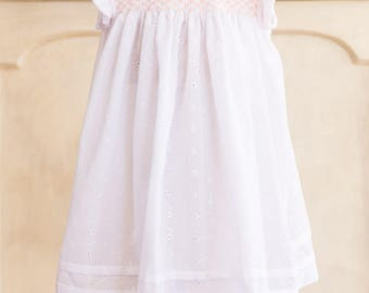 Hand-smocked cotton dress, age 12-18 months, white embroidered cotton with peach smocking