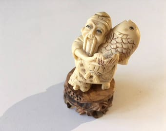 Vintage netsuke man with fish, comes with stand