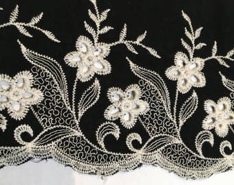 Black cotton fabric with a white floral embroidery design. BK204