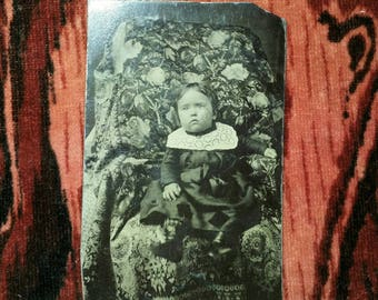 Antique tintype of a child seated on a gorgeous floral fabric