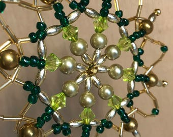 Eight-pointed star for a Christmas tree of beads in golden-green tones. Winter festive decoration. Handmade.