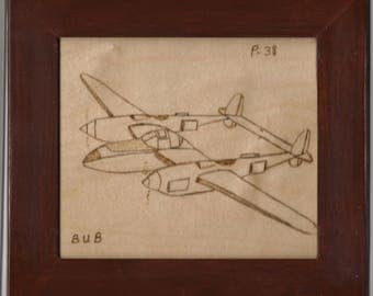 Wood burning picture of WWII P-38 Air plane in a wooden mahogany frame