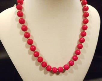 Red bead necklace with gold tone spacers.