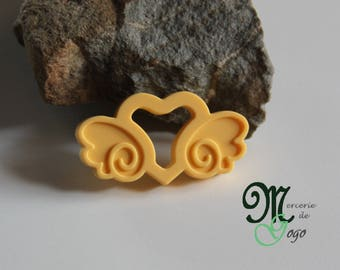 "Teething ring. ""Carriage heart"" shaped pale yellow."