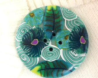 Round sewing button of 4.2 cm: flowers and green spirals.