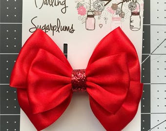 3 in. or 4in. Beautiful red satin bow with red glitter accent center. Alligator clip