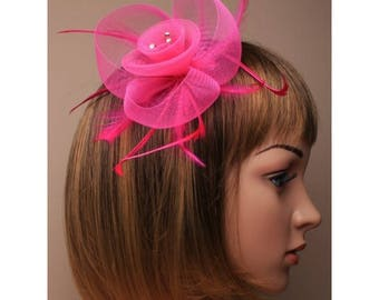 Coloured net and feather crystal centre fascinator on a clip and brooch pin.in pink Ideal for special occasions such as weddings and races.