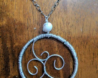 Flowing wire wrapped pendant with a white howlite bead